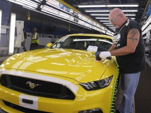 Wayne Moshier puts the finishing touches on a 2015 Mustang GT on the assembly line at Ford's Flat Rock Assembly Plant in August. About 57,000 Michigan workers from Detroit's Big Three will qualify for bonuses that range from $2,750 for workers at FCA US, to $6,900 for Ford Motor Co. employees and $9,000 for those at General Motors Co. (Photo: Detroit News file.)