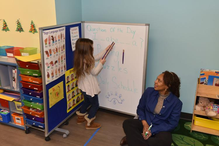 Saundra Harris, Hands of Hope's lead pre-kindergarten teacher, works with a child are the center.